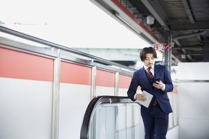 駅のエスカレーターでスマートフォンを見るスーツ姿の男性の写真素材 [FYI04676220]