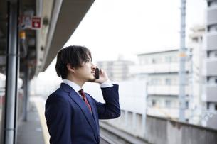 駅のホームで電話をするスーツ姿の男性の写真素材 [FYI04676221]