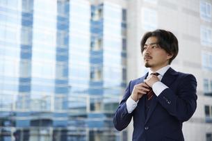 ビルの背景とネクタイを整えるスーツ姿の男性の写真素材 [FYI04676222]