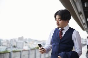 駅のホームでスマートフォンを見るスーツ姿の男性の写真素材 [FYI04676225]