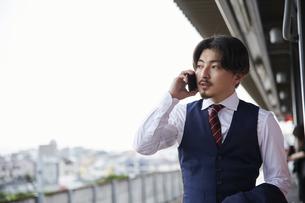 駅のホームで電話をするスーツ姿の男性の写真素材 [FYI04676226]