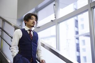 階段を降りるスーツ姿の男性の写真素材 [FYI04676227]