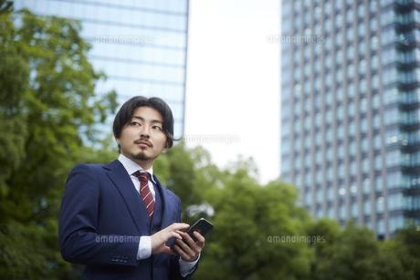 ビルの背景とスマートフォンを操作するスーツ姿の男性の写真素材 [FYI04676230]