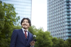 ビルの背景とスマートフォンを持つスーツ姿の男性の写真素材 [FYI04676231]