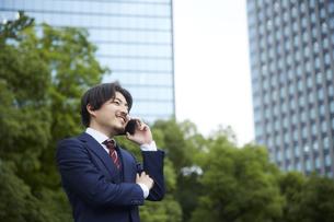 ビルの背景と電話をするスーツ姿の男性の写真素材 [FYI04676232]