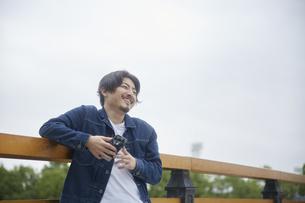手すりに肘をかける笑顔の男性の写真素材 [FYI04676234]