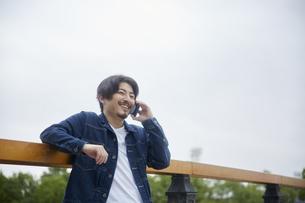 手すりに肘をかけて電話をする笑顔の男性の写真素材 [FYI04676235]