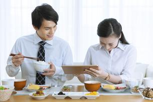 朝食を食べながらタブレットPCを見る夫婦の写真素材 [FYI04676297]