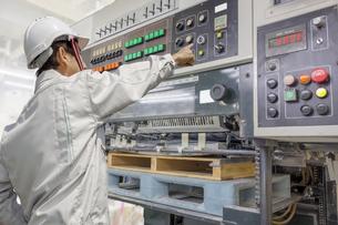 枚葉オフセット印刷機を操作する男性1人の後ろ姿の写真素材 [FYI04677264]