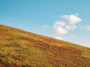【自然風景】雲が流れる青空の下の草原の丘 背景素材の写真素材 [FYI04677521]