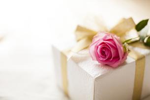 ベッドに置かれたプレゼントとバラの花の写真素材 [FYI04677817]