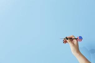 水色の背景にダーツを持った女性の手の写真素材 [FYI04678024]