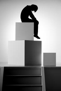 四角形を組み合わせ作られたオブジェに座り落ち込む人影の写真素材 [FYI04678090]