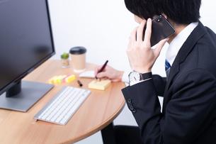 電話をかける若いビジネスマンの写真素材 [FYI04678233]