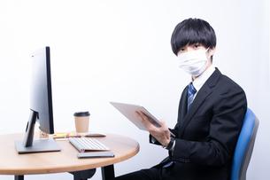 マスクをしてタブレットを操作する若いビジネスマンの写真素材 [FYI04678268]