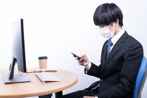 マスクをしてスマートフォンを操作する若いビジネスマンの写真素材 [FYI04678270]