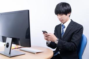 スマートフォンを操作する若いビジネスマンの写真素材 [FYI04678274]