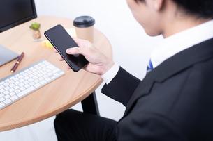 スマートフォンを操作する若いビジネスマンの写真素材 [FYI04678277]