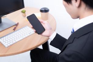 スマートフォンを操作する若いビジネスマンの写真素材 [FYI04678278]