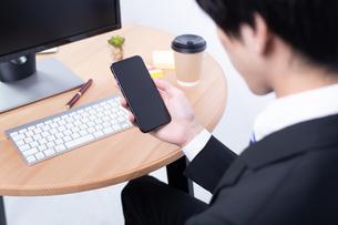 スマートフォンを操作する若いビジネスマンの写真素材 [FYI04678279]