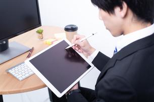 タブレットを操作する若い日本人ビジネスマンの写真素材 [FYI04678283]