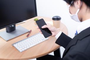 スマートフォンを操作する若い日本人ビジネスマンの写真素材 [FYI04678284]