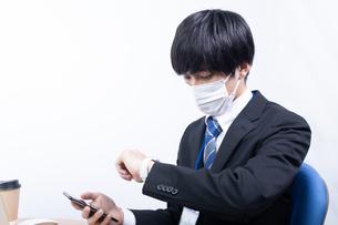 スマートウォッチを確認する若い日本人ビジネスマンの写真素材 [FYI04678293]