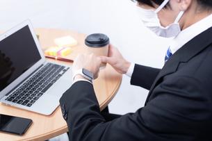 コーヒーを片手にスマートウォッチを確認する若い男性ビジネスマンの写真素材 [FYI04678296]