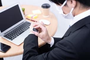 スマートウォッチを確認する若い日本人ビジネスマンの写真素材 [FYI04678298]