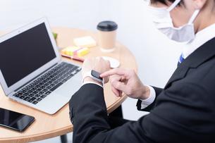 マスクをしてスマートウォッチを操作する若いビジネスマンの写真素材 [FYI04678299]