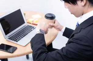 スマートウォッチを確認する若い日本人ビジネスマンの写真素材 [FYI04678301]