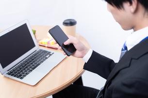 スマートフォンを操作する若い日本人ビジネスマンの写真素材 [FYI04678303]