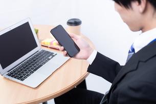スマートフォンを操作する若い日本人ビジネスマンの写真素材 [FYI04678305]
