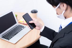 スマートフォンを操作する若い日本人ビジネスマンの写真素材 [FYI04678306]
