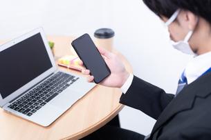 マスクをしてスマートフォンを操作する若い日本人ビジネスマンの写真素材 [FYI04678307]