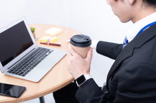 コーヒーを持つ若いビジネスマンの写真素材 [FYI04678319]