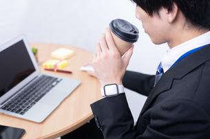 コーヒーを飲む若いビジネスマンの写真素材 [FYI04678320]