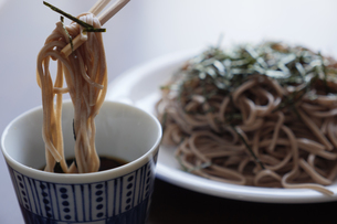 海苔のついた蕎麦を箸で汁につけるの写真素材 [FYI04679441]