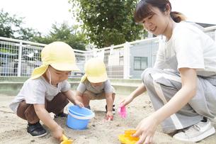 砂場で遊ぶ子供と女性の保育士の写真素材 [FYI04679875]