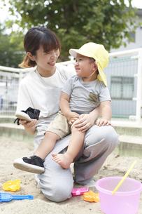 砂場で子供を抱える女性の保育士の写真素材 [FYI04679876]
