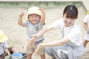 砂場で遊ぶ子供と女性の保育士の写真素材 [FYI04679877]