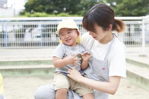 砂場で子供を抱える女性の保育士の写真素材 [FYI04679878]