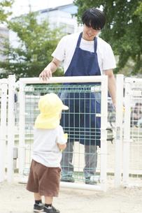 砂場の扉を開ける男性の保育士と子供の写真素材 [FYI04679879]