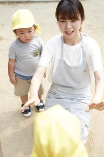 公園で遊ぶ子供と女性の保育士の写真素材 [FYI04679880]
