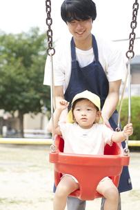 ブランコで遊ぶ子供と男性の保育士の写真素材 [FYI04679881]