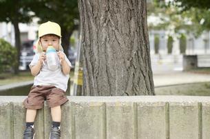 公園で座ってお茶を飲む子供の写真素材 [FYI04679882]