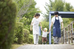 子供と手を繋ぐ男女の保育士の写真素材 [FYI04679883]