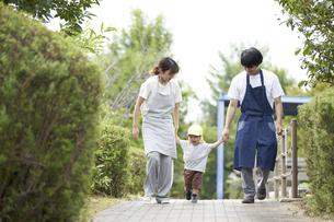 子供と手を繋ぐ男女の保育士の写真素材 [FYI04679884]