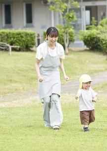 芝生で遊ぶ子供と女性の保育士の写真素材 [FYI04679886]