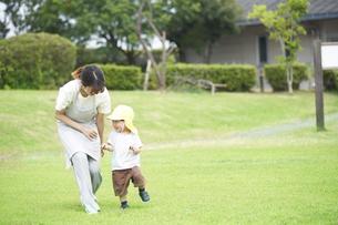 芝生で遊ぶ子供と女性の保育士の写真素材 [FYI04679887]
